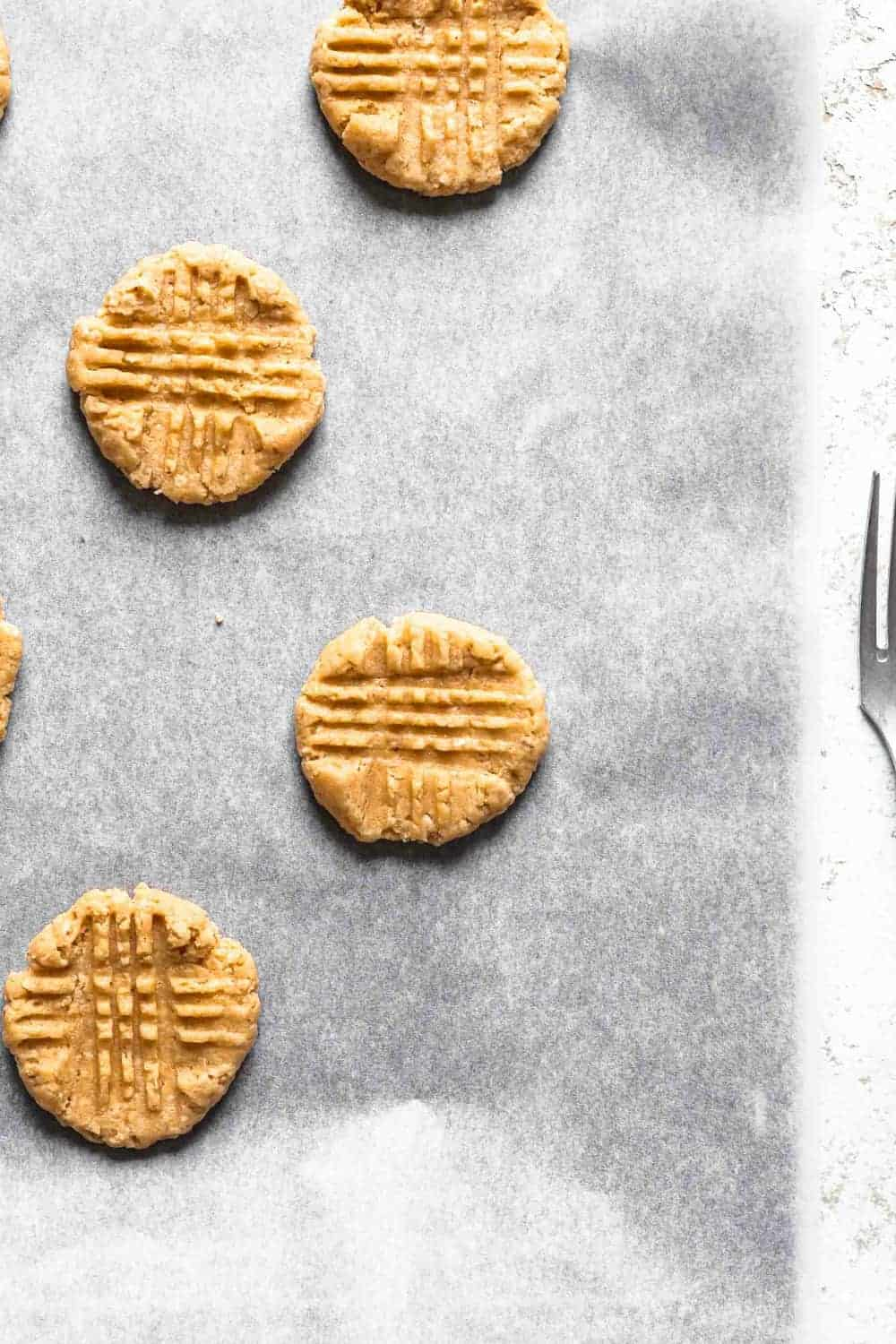 Unbaked peanut butter cookies on a parchment-lined baking sheet