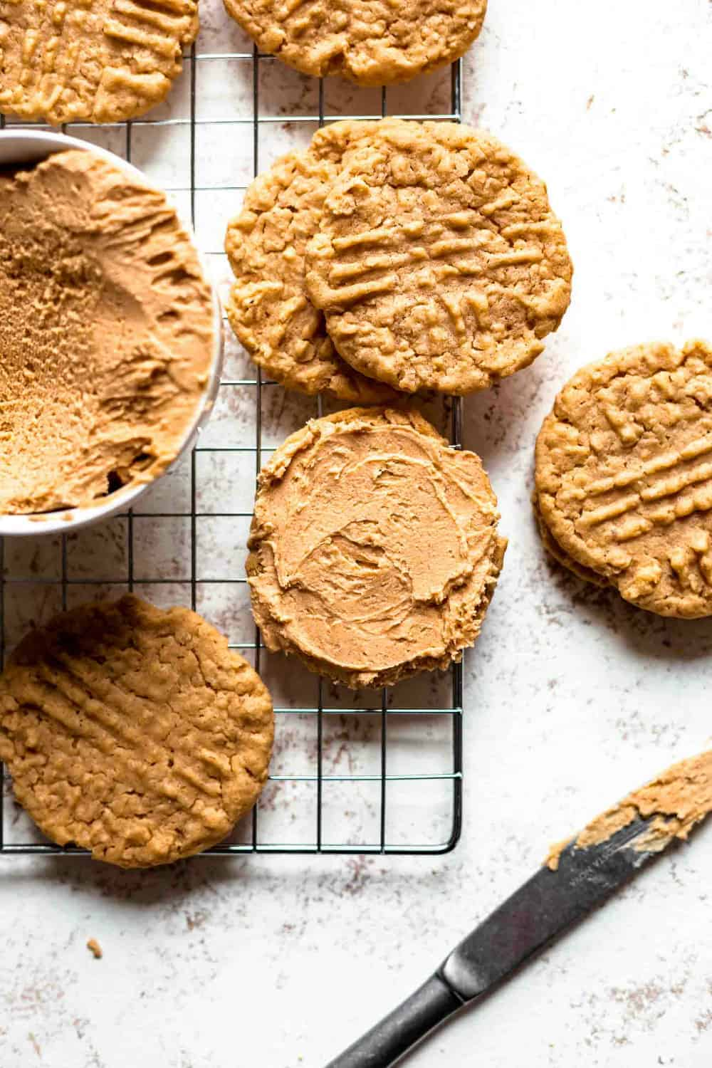 Bowl of peanut butter filling surrounded by peanut butter cookies. One of the cookies is topped with peanut butter filling