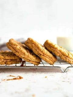 Peanut butter sandwich cookies stacked on a baking rack with a glass of milk in the background