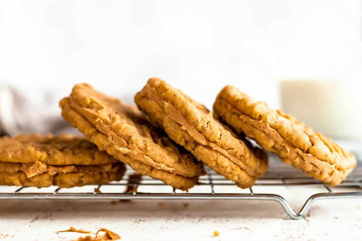 Close up of four peanut butter sandwich cookies laying on their side on a baking rack