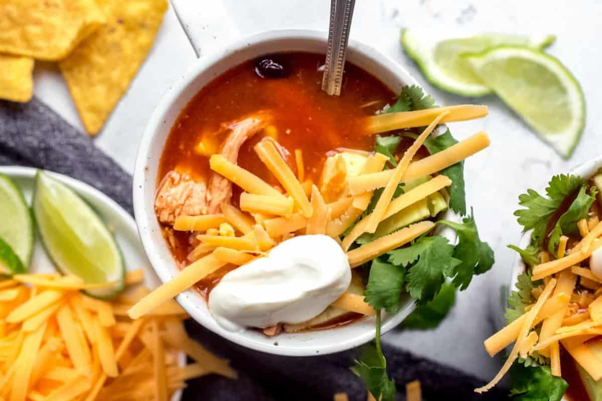 Spoon in a white mug of tortilla soup topped with cheese and sour cream