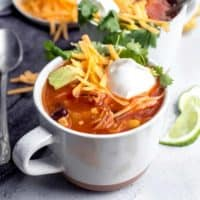 Tortilla soup in a white mug, topped with cheese and sour cream