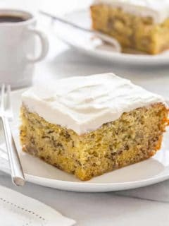 Slice of frosted moist banana cake on a white cake next to a silver fork
