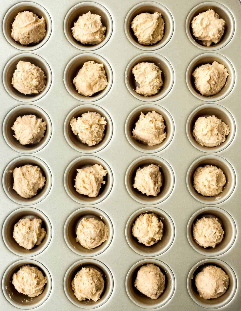 Peanut butter cookie dough scooped into a mini muffin tin to make Peanut Butter Cup Cookies