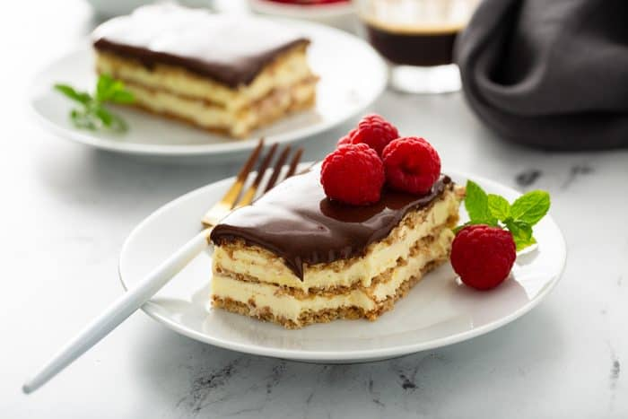 Slice of eclair cake topped with fresh raspberries on a white plate with a second slice of cake in the background