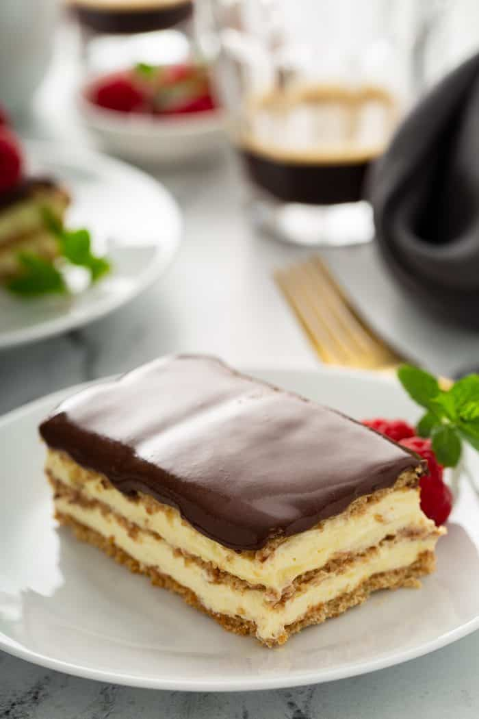 Slice of eclair cake on a white plate with cups of coffee and more plates in the background