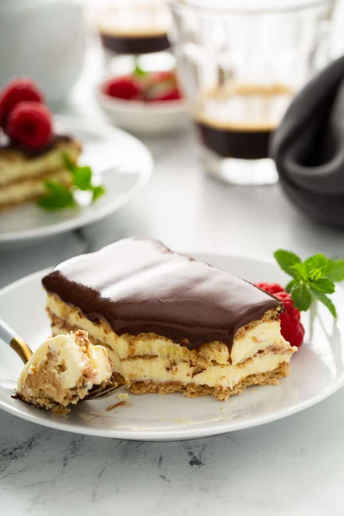 Fork holding a bite of eclair cake on a white plate next to a full slice of eclair cake