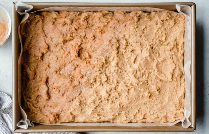 Dough for snickerdoodle blondies in a pan, with half of the dough covered with cinnamon-sugar