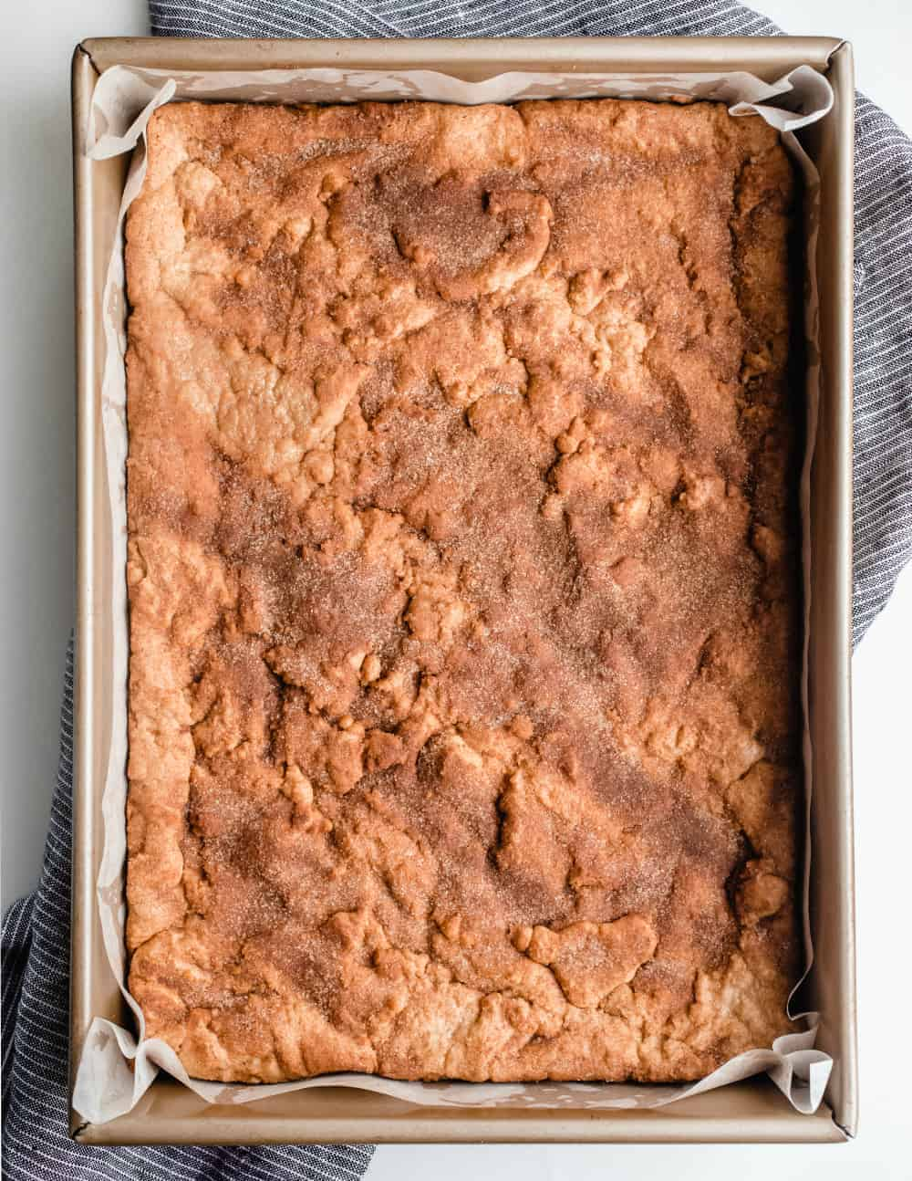 Freshly-baked snickerdoodle blondies in a parchment-lined pan, ready to be cut