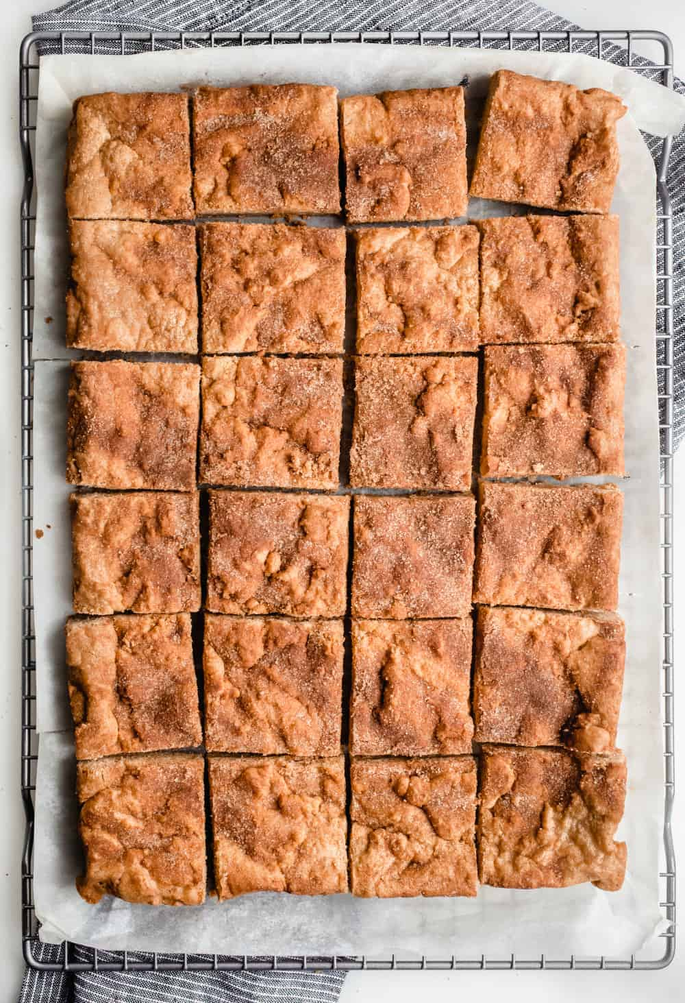 Baked and cut snickerdoodle blondies in a parchment-lined cooling rack