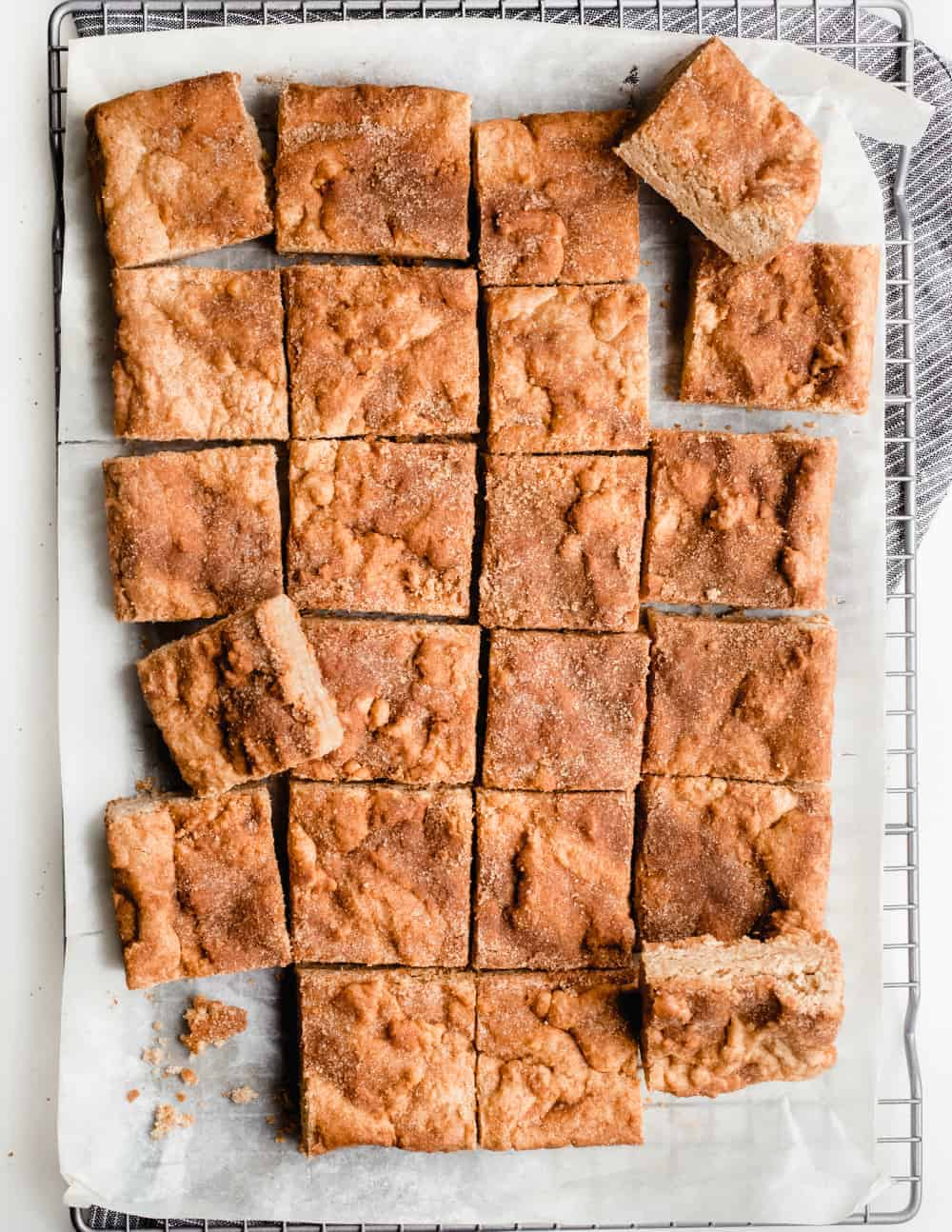 Snickerdoodle blondies scattered on a cooling rack