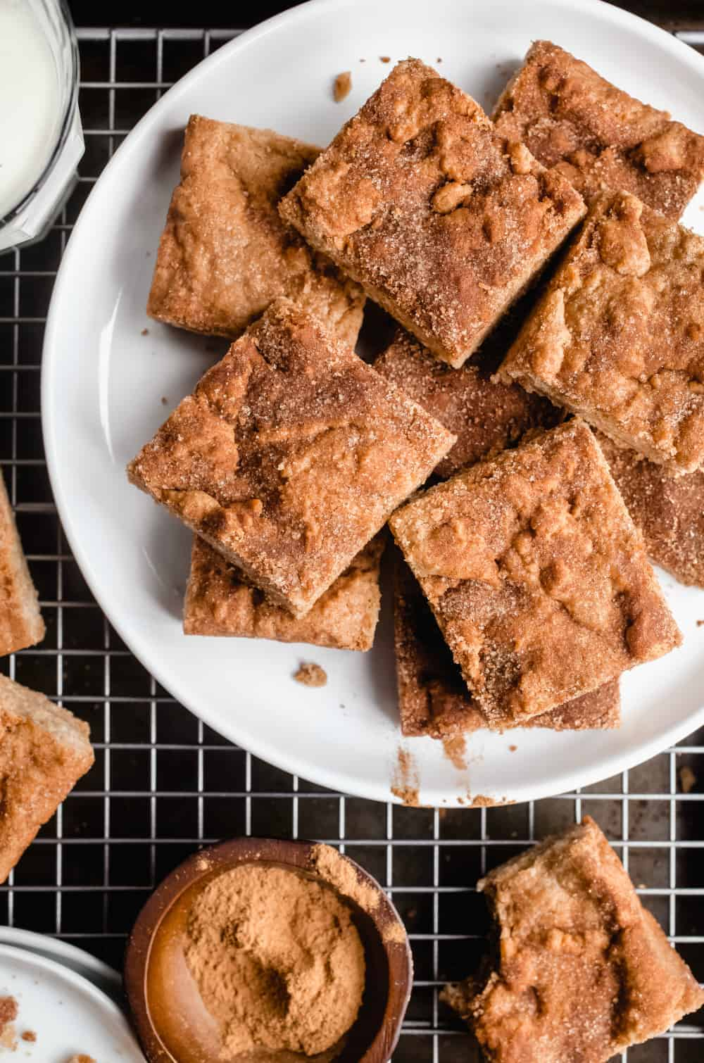 Cut snickerdoodle blondies arranged on a white plate that is set on a wire rack