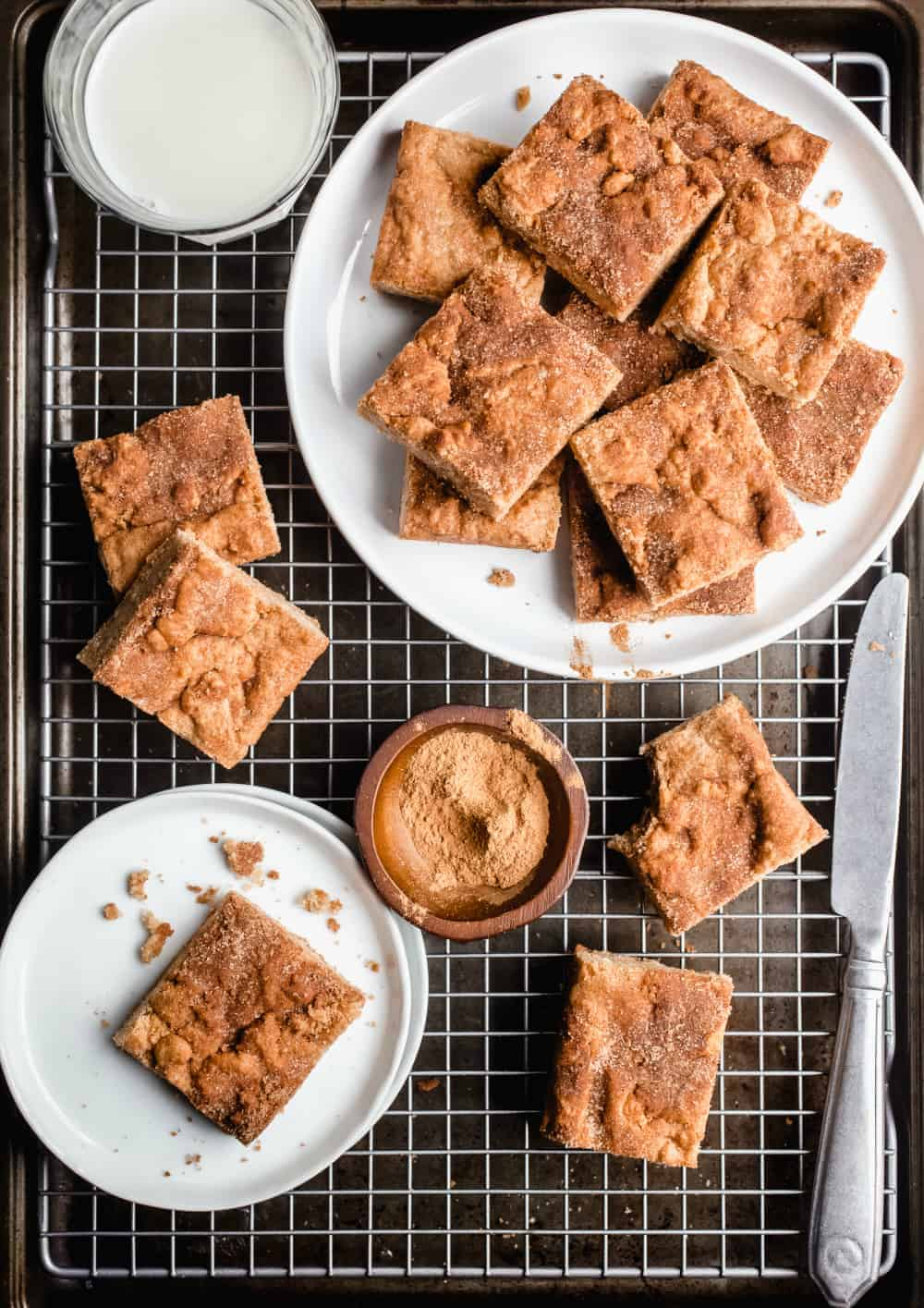 White plate filled with snickerdoodle blondies on top of a wire rack alongside several scattered blondies