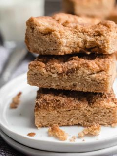 Three stacked snickerdoodle blondies on a white plate. The top blondie has a bite taken out of it.