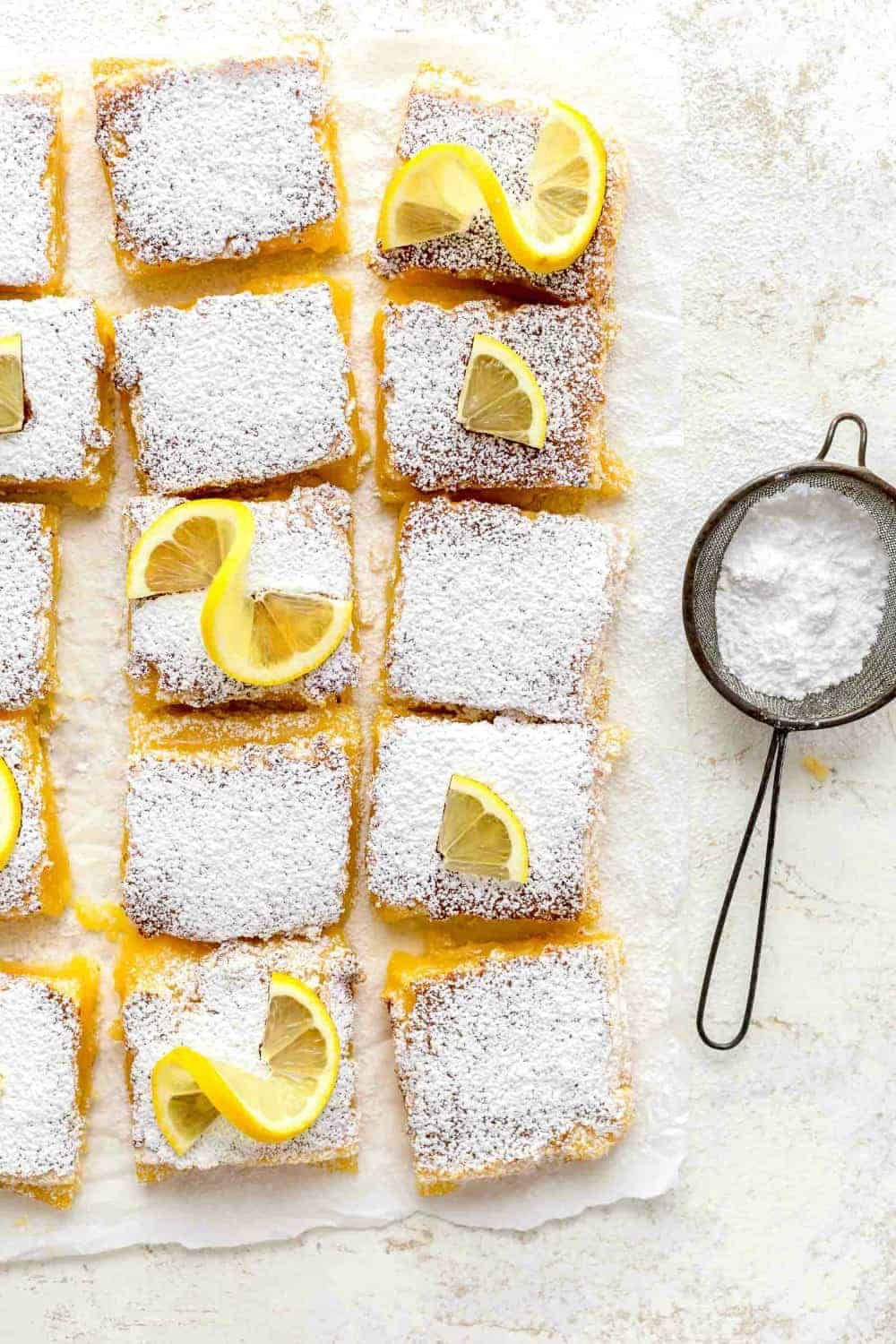 Overhead view of sliced homemade lemon bars next to a duster filled with powdered sugar