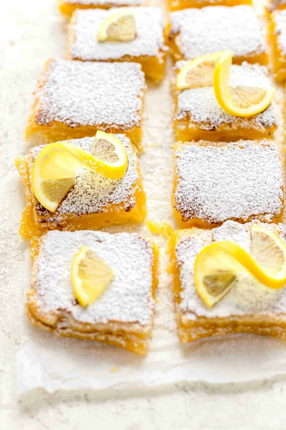 Overhead view of homemade lemon bars, sliced and topped with powdered sugar and lemon slices