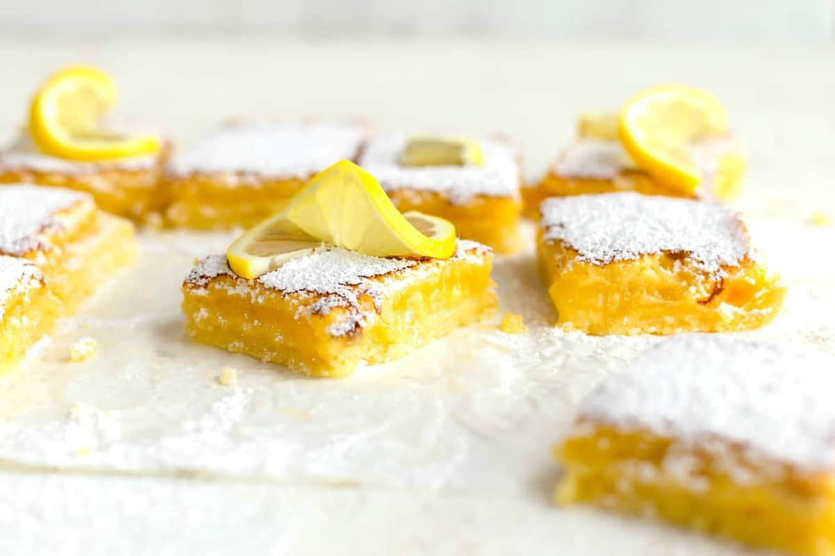 45-degree view of homemade lemon bars on parchment paper, topped with powdered sugar and lemon twists