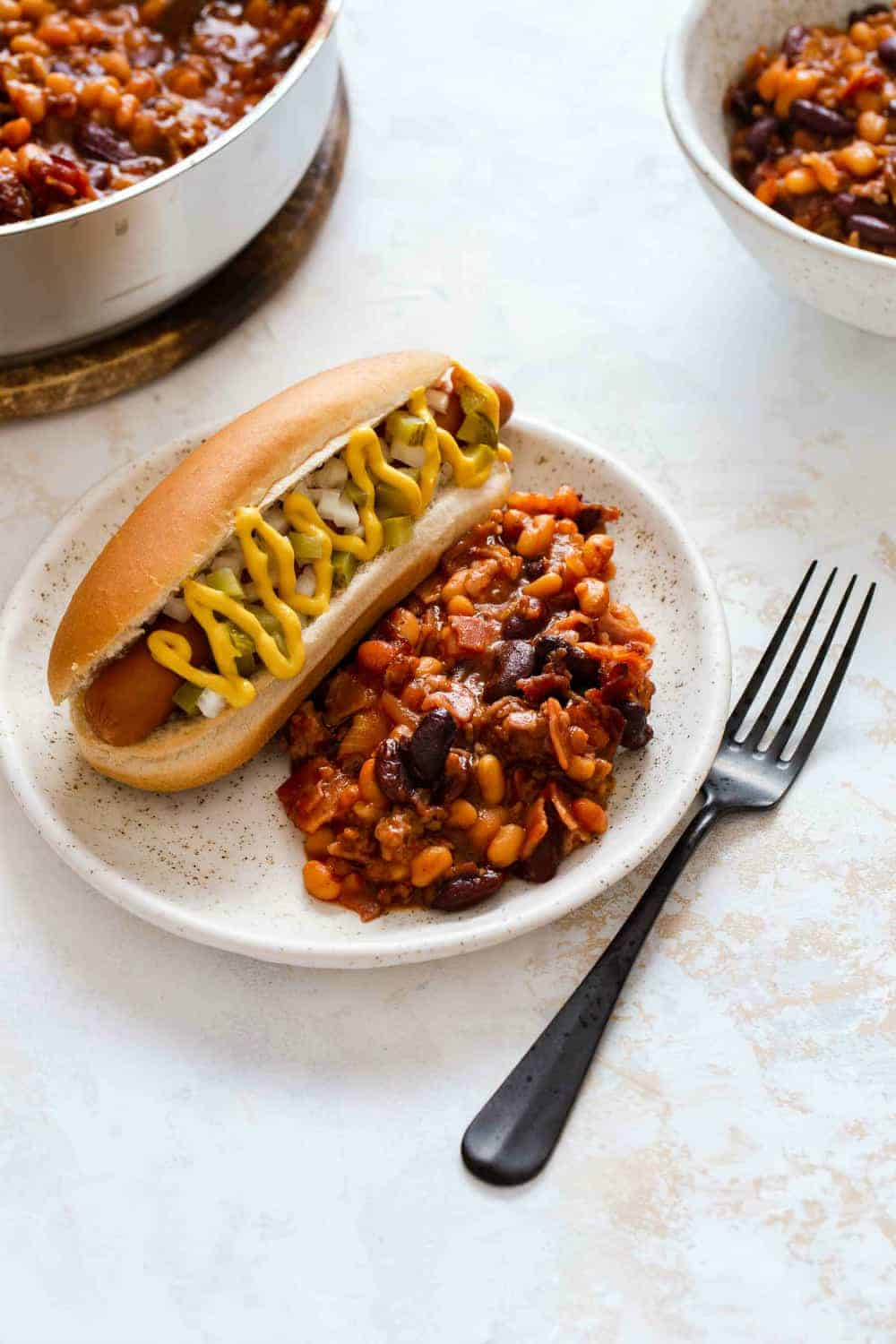 Old fashioned baked beans and a hot dog on a white plate