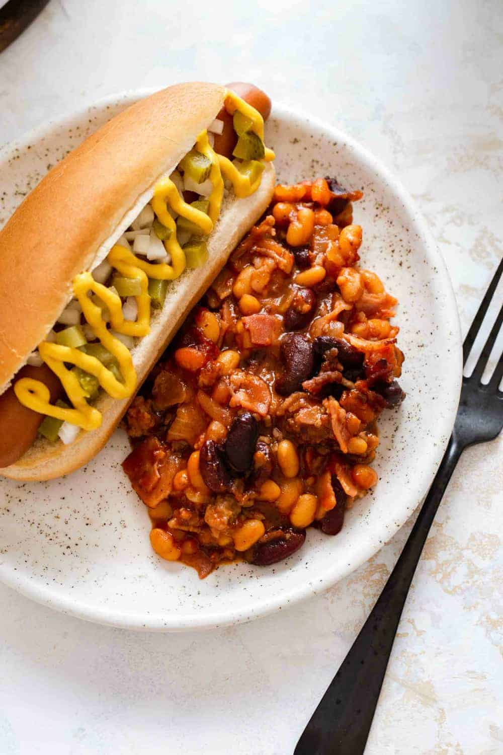 Close up of a plate with old fashioned baked beans and a hot dog