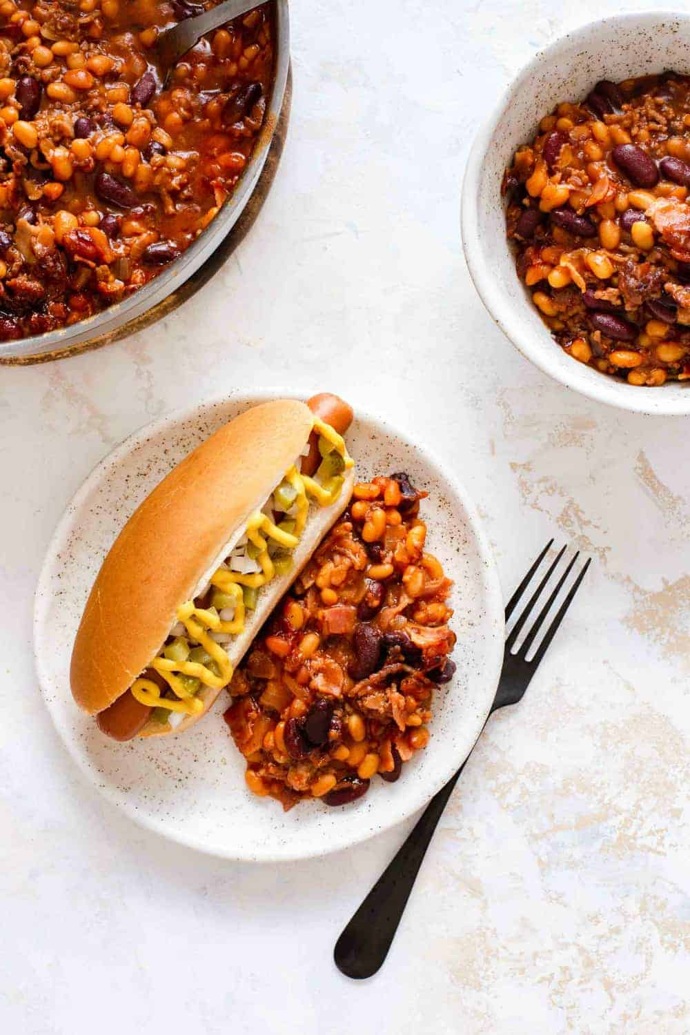 Hot dog and old fashioned baked beans on a white plate next to bowls of baked beans