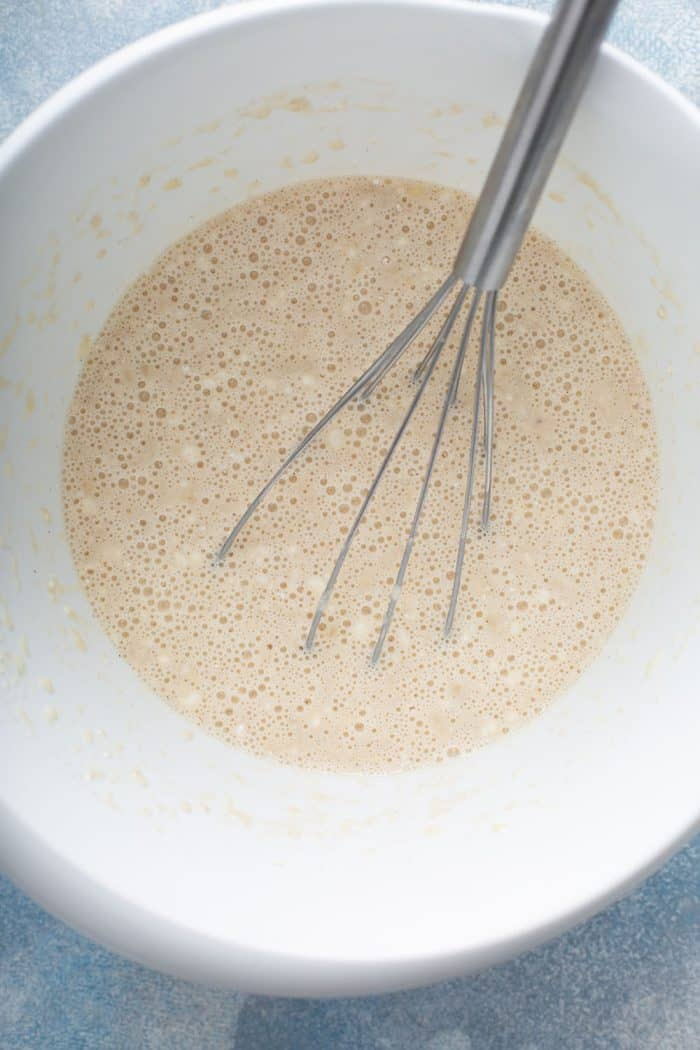 Whisk stirring banana pancake batter inside a white mixing bowl