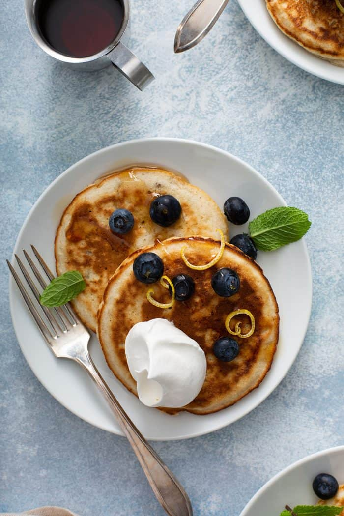 Two banana pancakes topped with blueberries, whipped cream and mint on a white plate set on a light blue surface