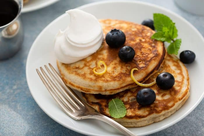 Fork and two banana pancakes, topped with blueberries and whipped cream, on a white plate