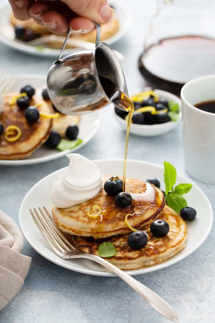 Syrup being poured over 2 banana pancakes topped with blueberries and whipped cream on a white plate. Two more plates of pancakes and a mug of coffee are in the background