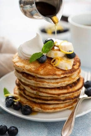 Stack of banana pancakes on a white plate, topped with sliced bananas, blueberries and whipped cream, with syrup being drizzled on top