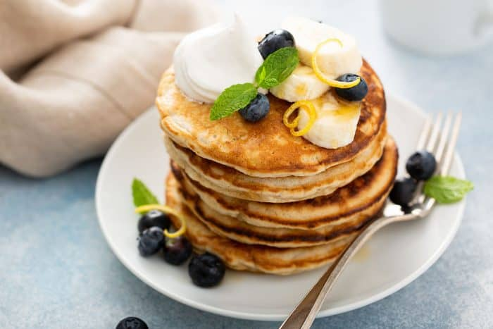 Stack of banana pancakes topped with blueberries, sliced bananas and whipped cream on a white plate, next to a fork