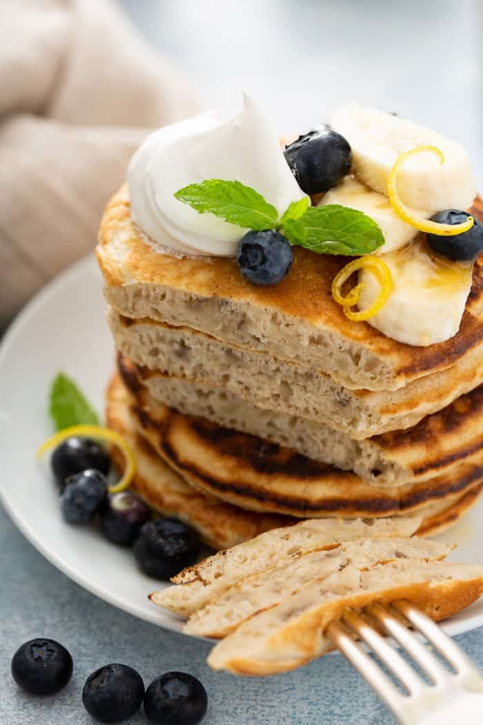 Stack of banana pancakes topped with blueberries, sliced bananas, and whipped cream next to a fork with a bite of pancakes on it