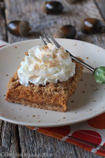 A piece of a pumpkin streusel cheesecake bar topped with whipped cream on a plate
