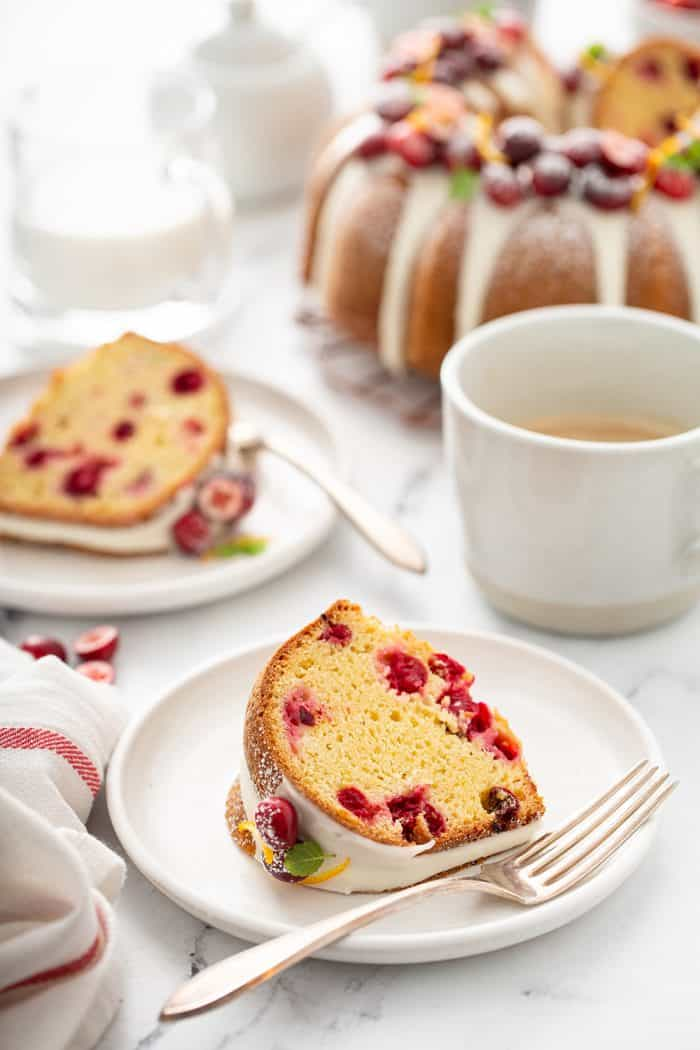 Two white plates with slices of cranberry orange bundt cake with a full bundt cake in the background