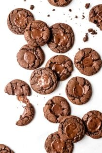 chocolate mint cookies scattered across a white surface, with some broken in half.