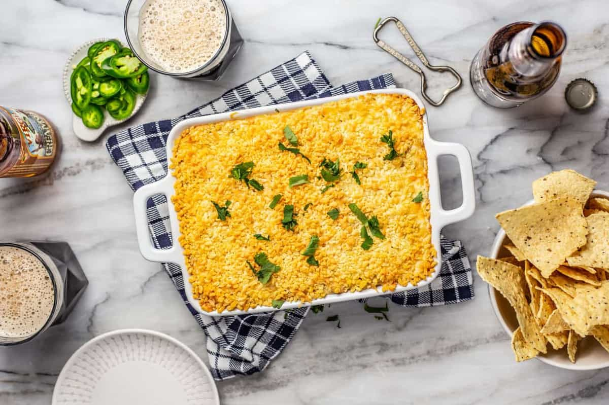 Baked jalapeno popper dip in a white baking dish surrounded by chips and beer