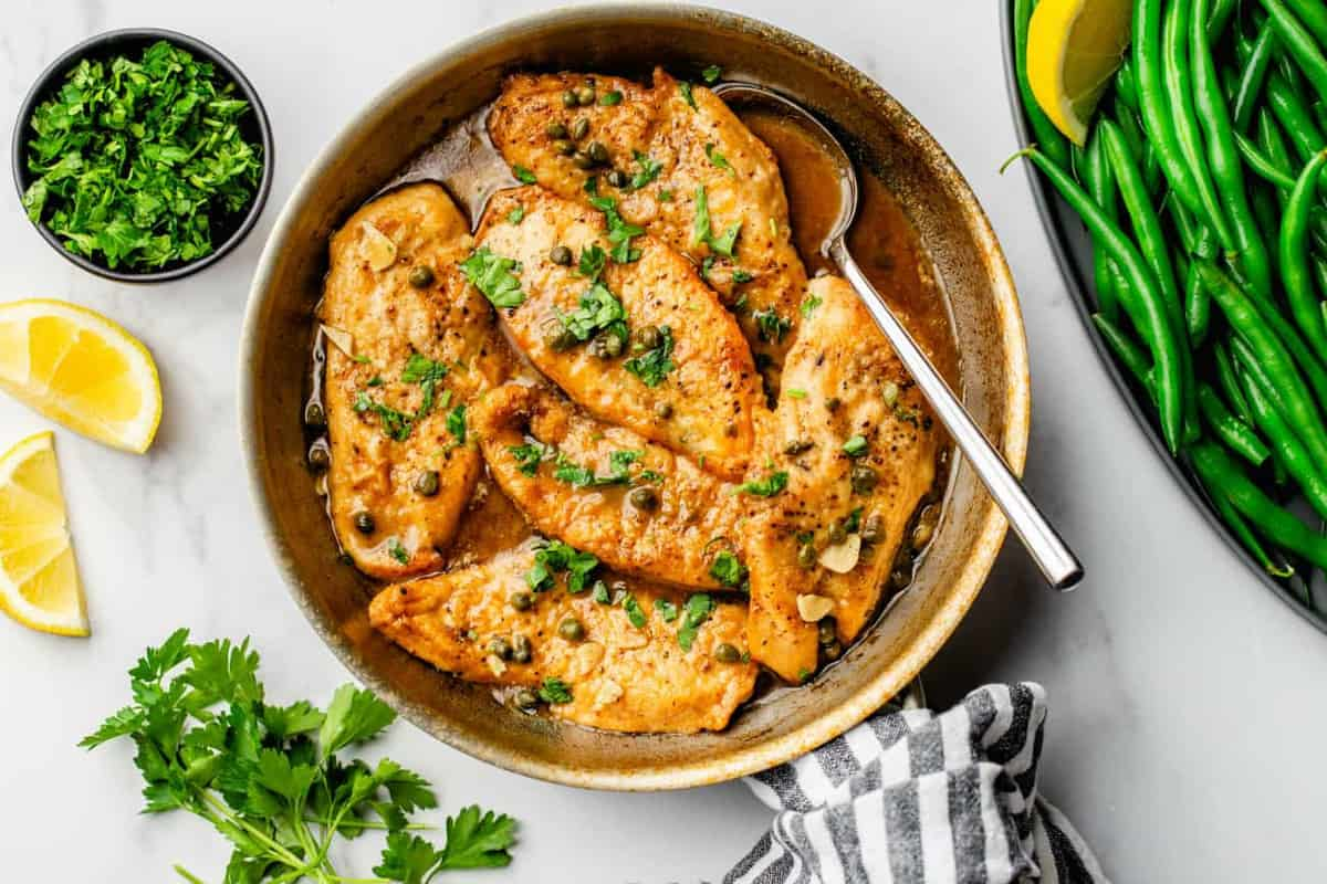 Chicken Piccata is served in a bright lemon-caper sauce and sprinkled with parsley to round out the dish.