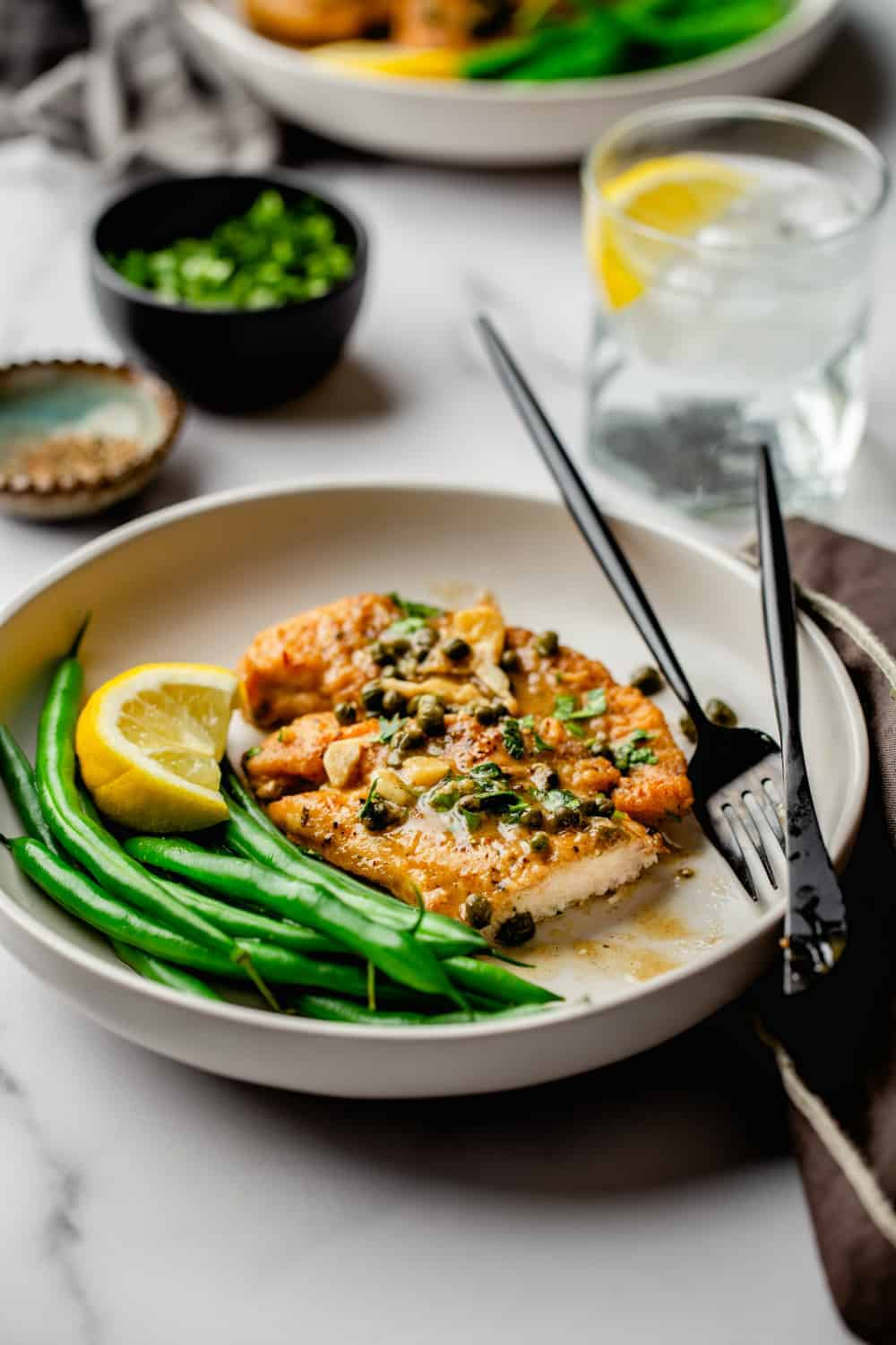 Chicken Piccata on a plate served with green beans and a lemon wedge with a black fork and knife.