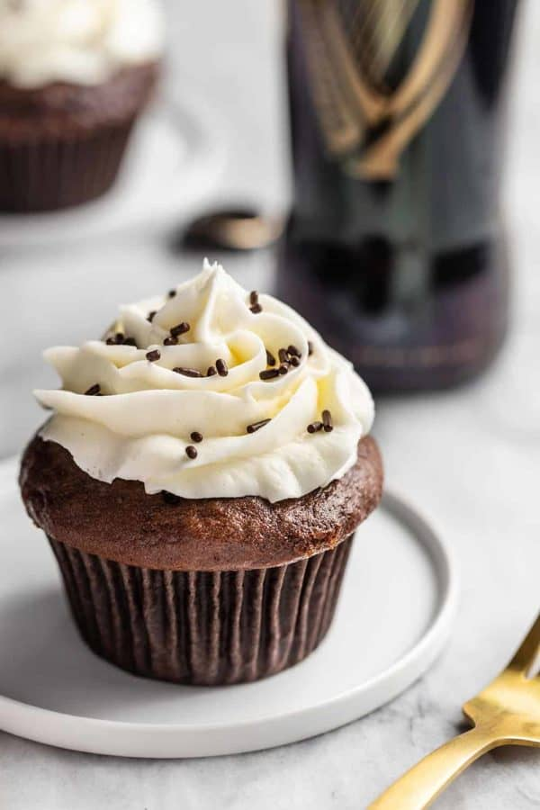 Guinness cupcake on a white plate with a bottle of Guinness in the background