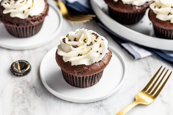 Frosted Guinness cupcake on a white plate with a platter of cupcakes in the background
