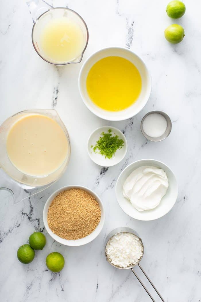 Overhead view of the ingredients for key lime pie bars measured into various bowls on a marble counter