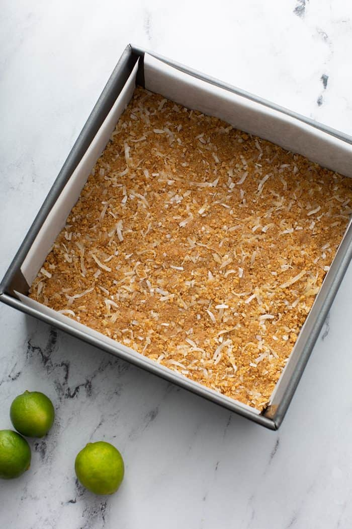 Coconut graham cracker crust in a parchment-lined baking pan on a marble countertop