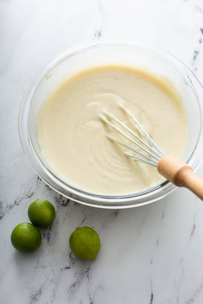 Key lime pie bar filling being whisked together in a glass mixing bowl on a marble surface