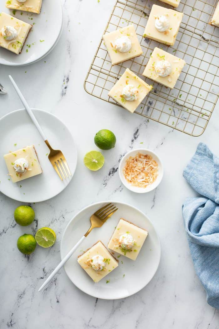 Overhead view of three white plates holding key lime pie bars on a marble counter next to a wire cooling rack holding more key lime pie bars