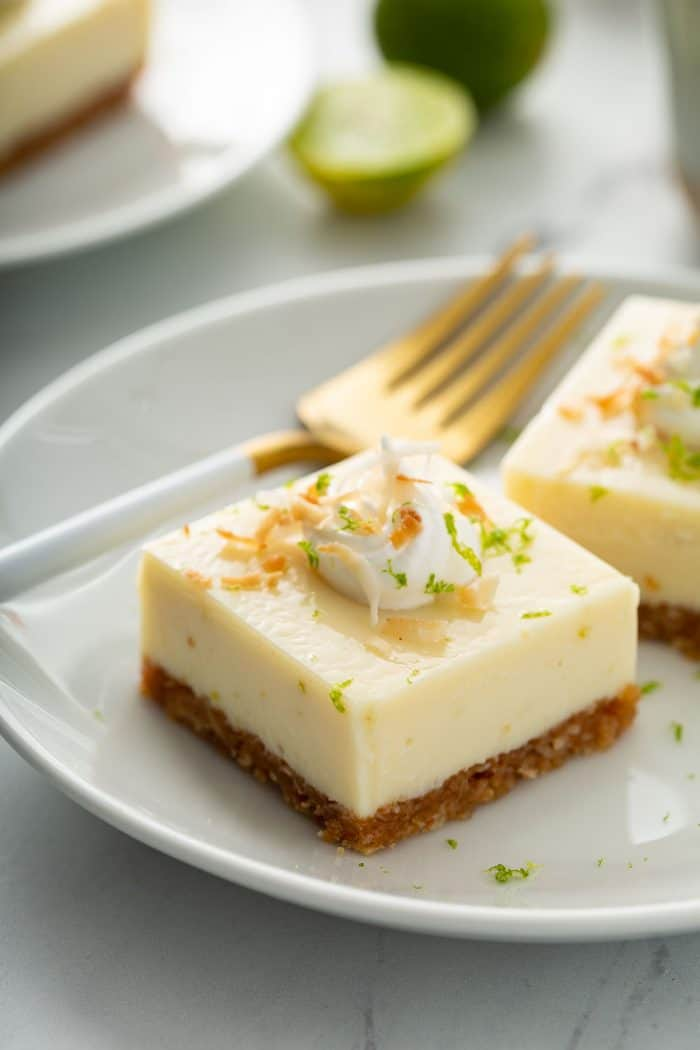Close up of two key lime pie bars topped with whipped cream and toasted coconut on a white plate, next to a gold fork with a white handle