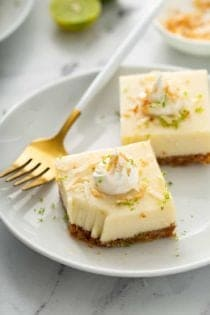 Two key lime pie bars on a white plate next to a gold fork with a white handle. The corner of one bar has a bite taken out of it