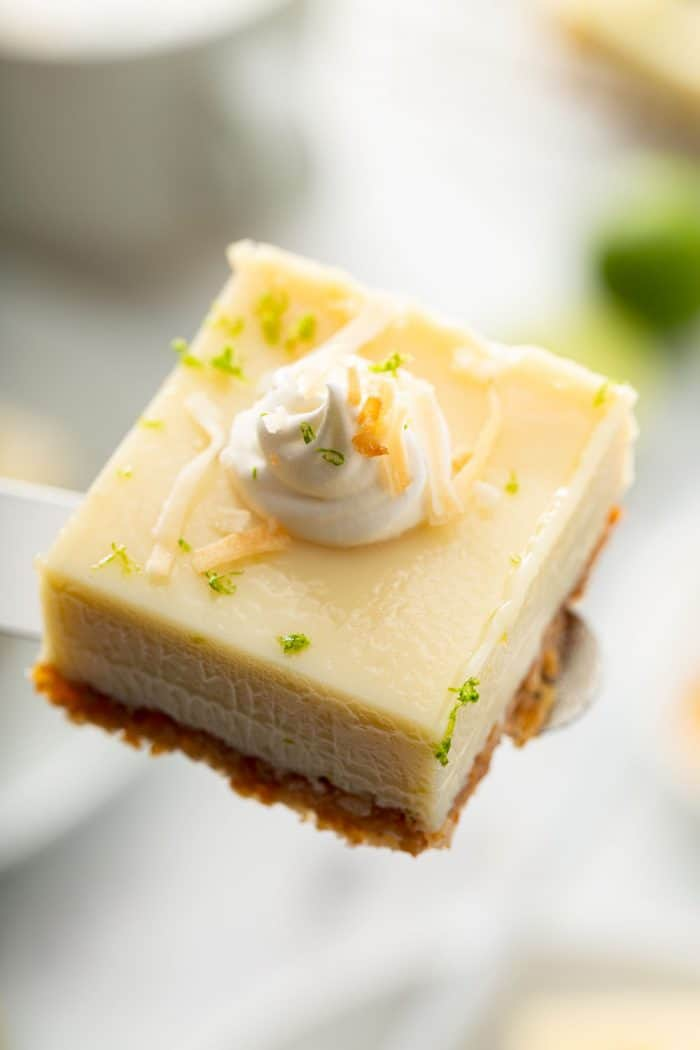 Key lime pie bar topped with whipped cream and toasted coconut being held up to the camera by an offset spatula