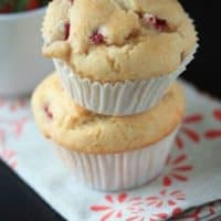 Two strawberry lemon muffins stacked on top of each other on a white and red decorated napkin