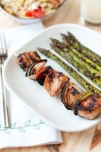 A Greek Kabob on a plate with a side of asparagus