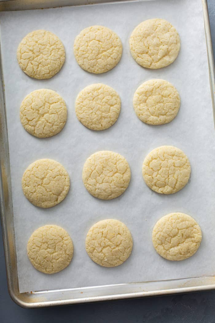 Baked chewy lemon sugar cookies on a parchment-lined baking sheet