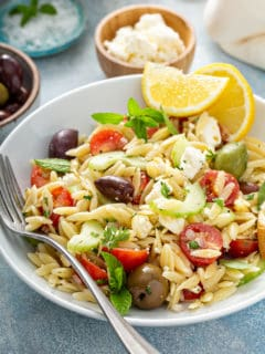 White plate of greek orzo salad garnished with wedges of lemon